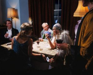 Adults in fancy dress, playing cards at table, man by window outdoors
